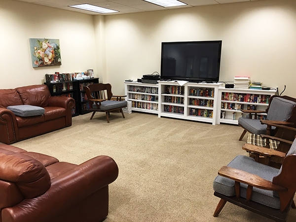 Student lounge includes couches, TV and bookcase of movies and books.