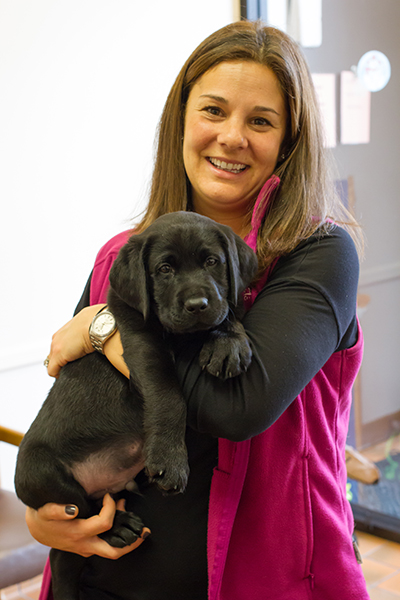 A woman holding a black lab pup that she sponsored.