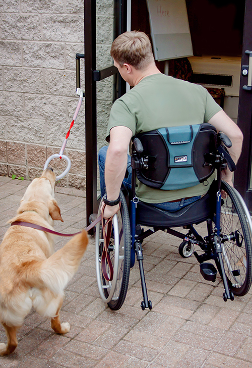 Will's service dog holding a door open for him to enter.