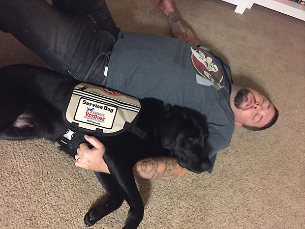 A black lab lying with his handler during a seizure.