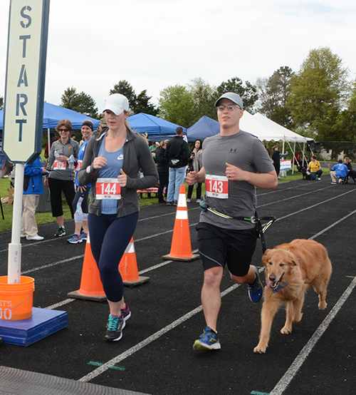 A man, woman, and dog cross the finish line at the 2017 event.