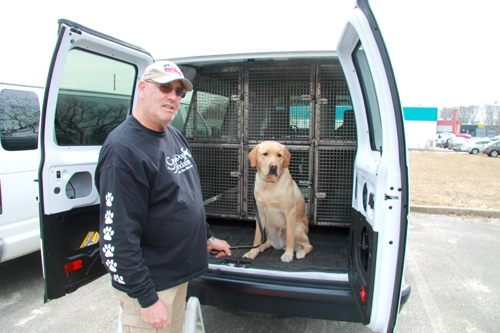 A taxi team member and a yellow Lab at the back of a Foundation van.